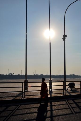 El sol grapado en la farola y un monje paseando a orillas del Mekong.